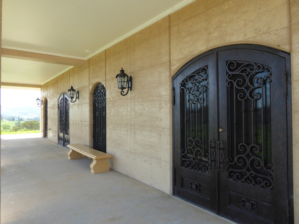 Rammed earth arched doorway, ironwork doors