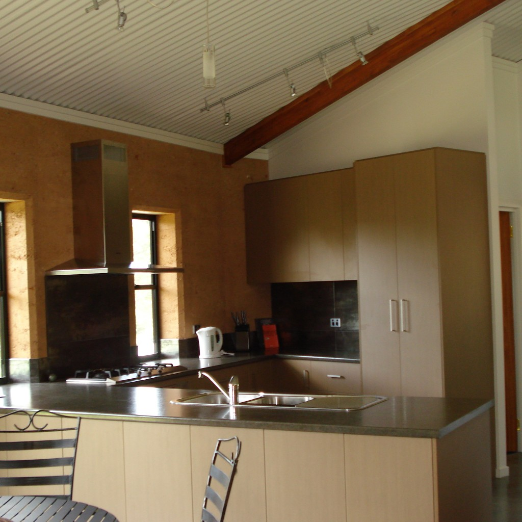 Rammed earth kitchen wall, ritek ceiling