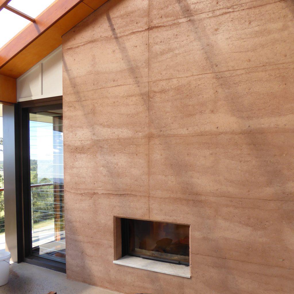 External side rammed earth wall fireplace