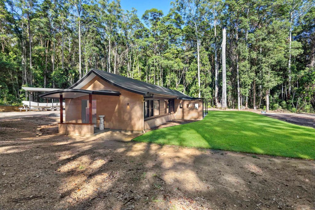 Rammed earth cottage, curved truss, sustainable living