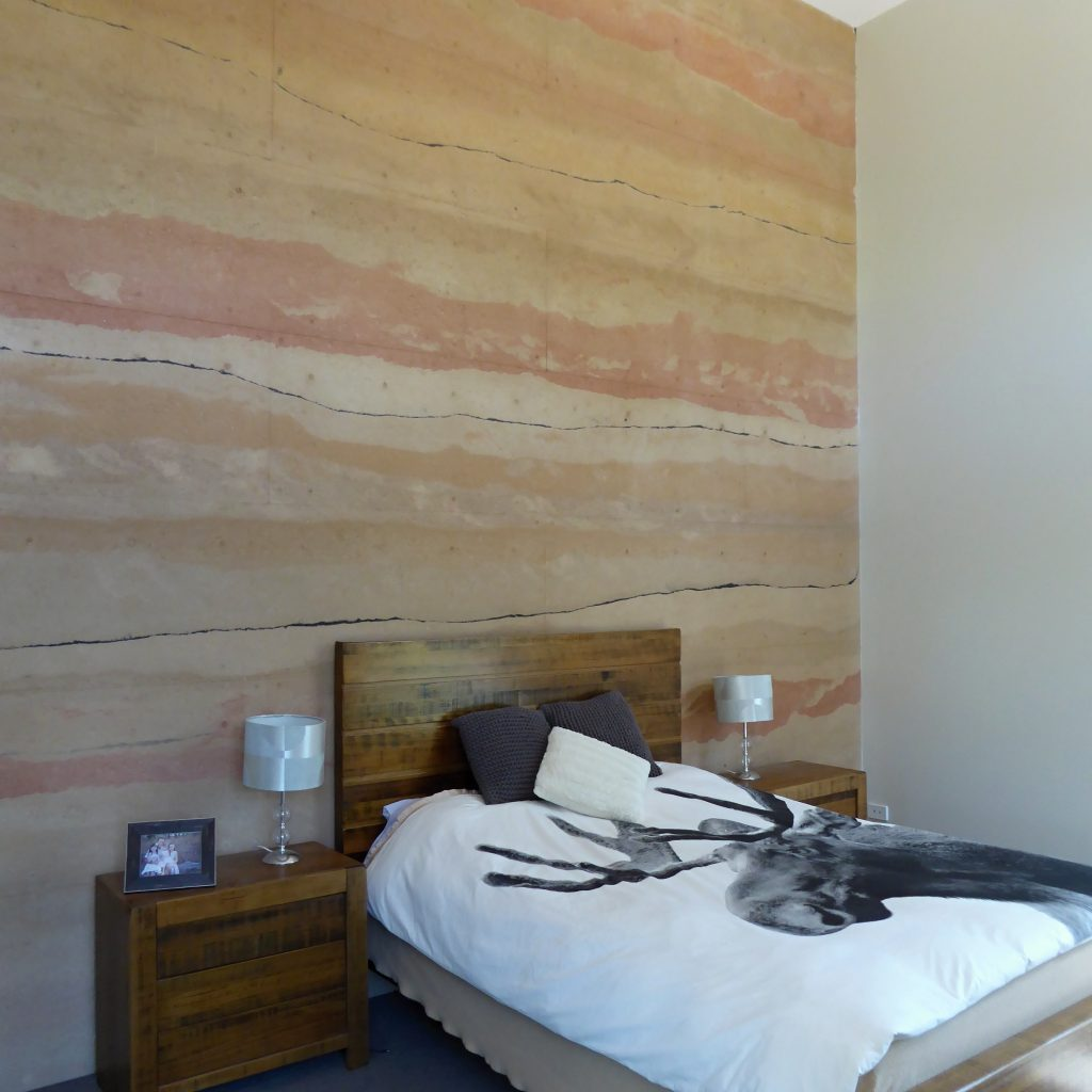 colourful rammed earth bedroom wall