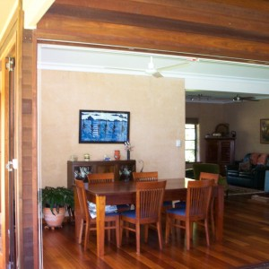 Subtropical rammed earth home with big stacking doors to deck.