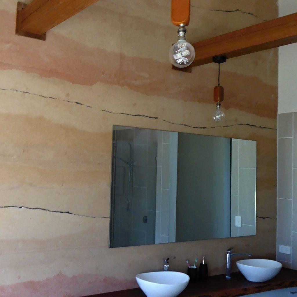 colourful rammed earth bathroom wall