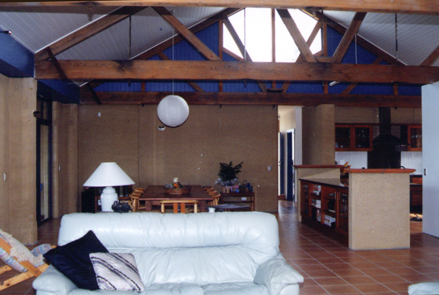 Rammed earth open plan living area with exposed trusses, Queensland